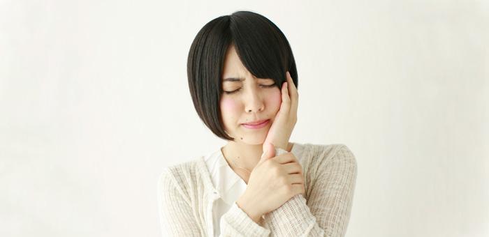 顎をおさえる女性